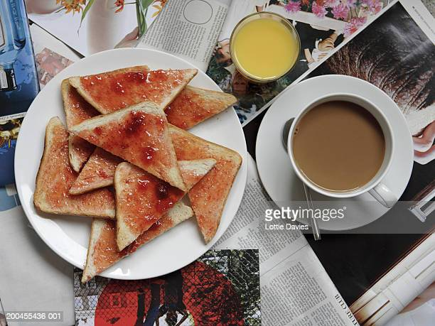 Plate of toast and jam on newspapers with cup of tea and orange juice
