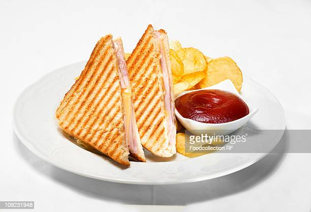 Plate of toasted ham and cheese sandwiches with ketchup and crisps