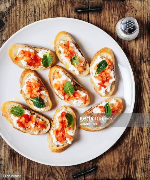 plate of tomato bruschetta on wooden background - appetizer stock pictures, royalty-free photos & images