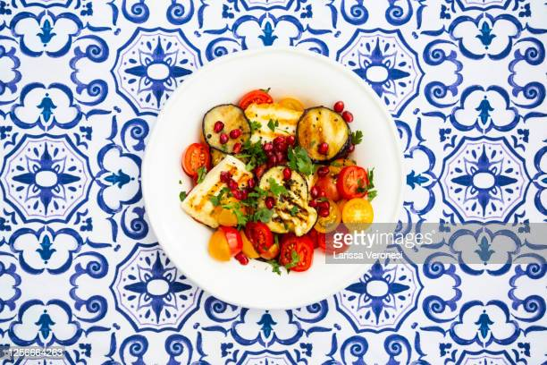 plate of tomato salad, grilled vegetables, and halloumi cheese - larissa veronesi stock-fotos und bilder