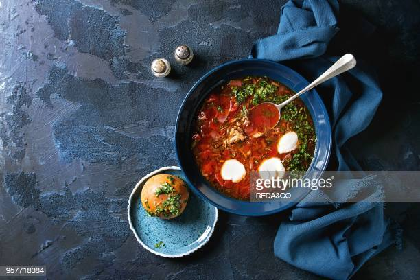 Plate of traditional beetroot borscht soup with sour cream and fresh coriander served with garlic bread buns pampushka with blue textile over dark...
