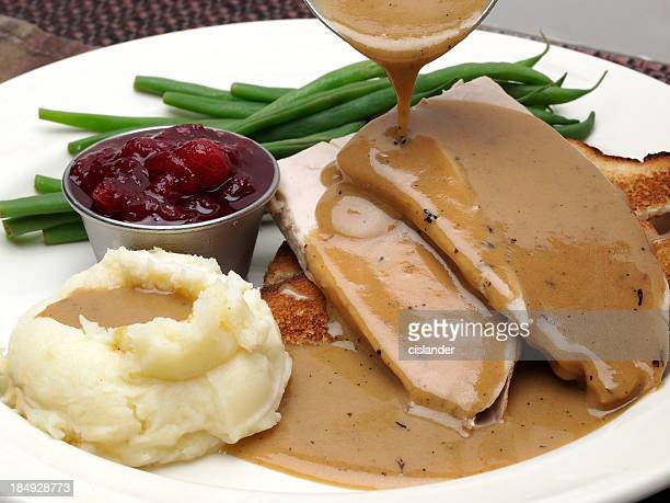 plate of turkey with gravy, mashed potatoes and green beans - cranberry sauce stock photos and pictures