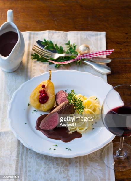 plate of venison filet with ribbon noodles, stuffed pear and red wine sauce - carne de cervo - fotografias e filmes do acervo
