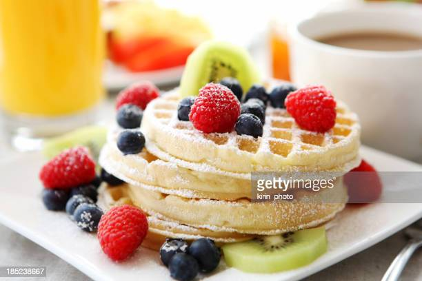 A plate of waffles topped with berries, sugar and kiwi