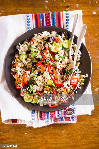 plate of warm salad with brown rice, roasted eggplant, zucchini, red and green bell pepper, mushroom, onion, top view - arroz integral - fotografias e filmes do acervo