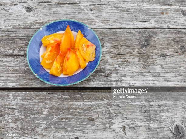 plate of yellow tomatoes on a wooden table - charleroi stock pictures, royalty-free photos & images