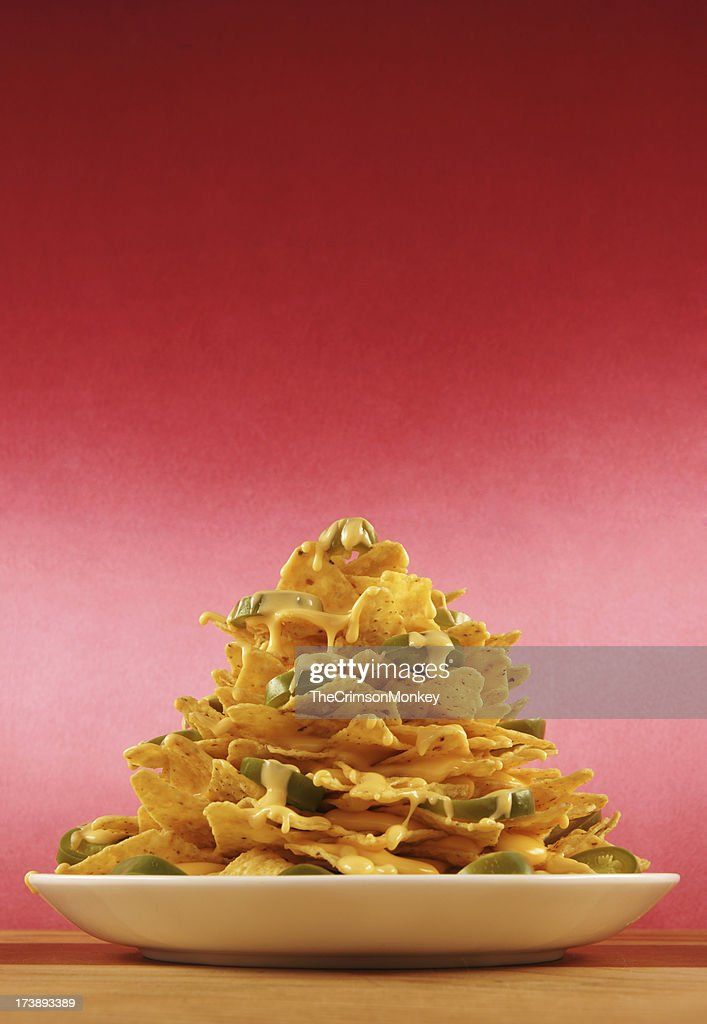 Plate piled very high with nachos : Stock Photo