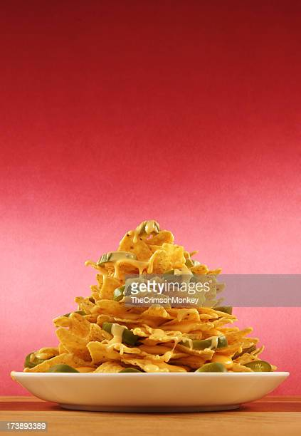 plate piled very high with nachos - cheese sauce stock photos and pictures