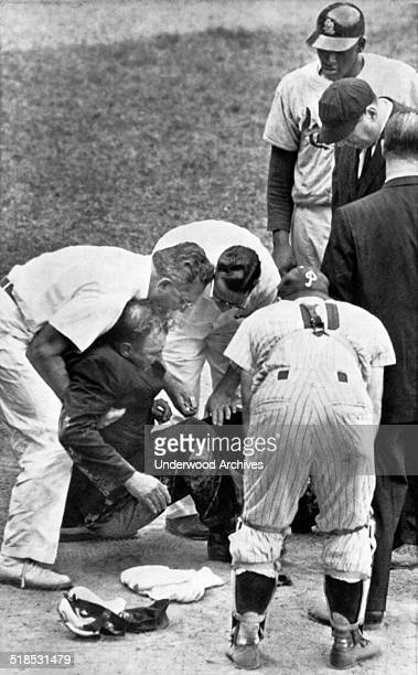 Plate umpire Mel Steiner is helped to his feet after he was felled by a foul tip from the bat of Cardinal's pitcher Bob Gibson standing at rear right...