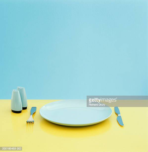 plate, utensils and salt and pepper shakers on table - plate stock pictures, royalty-free photos & images