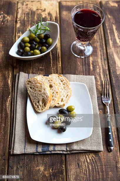 Plate with baguette slices and olives and a glass of red wine