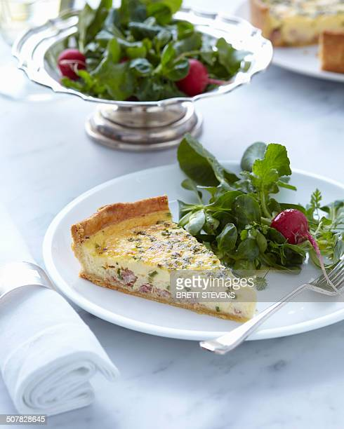 Plate with classic quiche slice and fresh salad