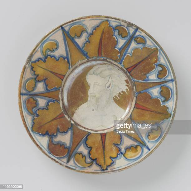 Plate with deepened flat multicolored painted with satyr with pointed ears and beard Round plate of multicolored painted majolica with a deepened...