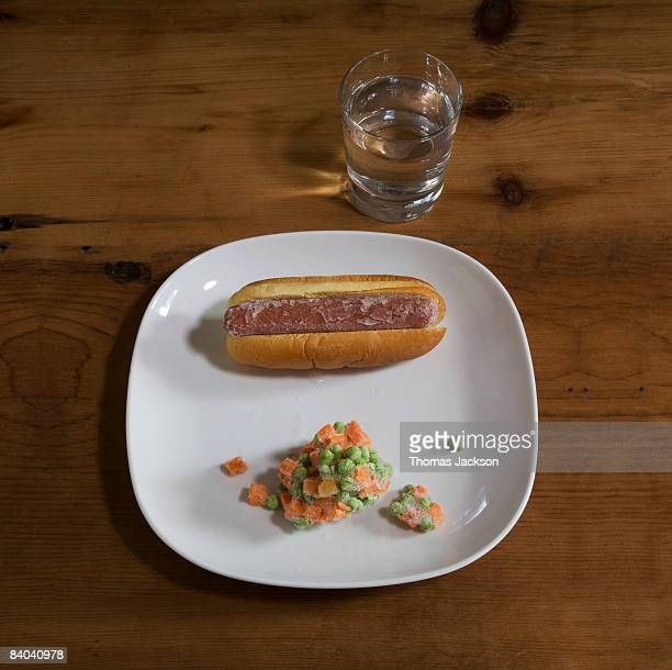 Plate with frozen hot dog and frozen vegetables