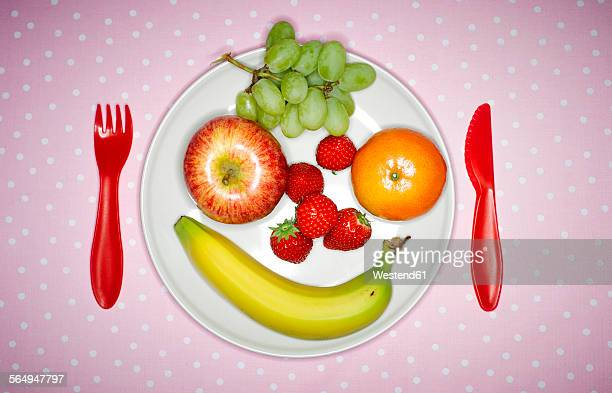 Plate with fruits building funny face and red plastic cutlery on pink cloth