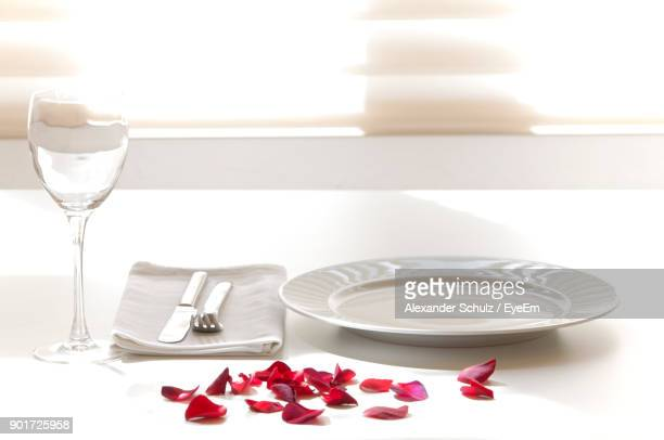 plate with napkin and wineglass on table - rose petals stock pictures, royalty-free photos & images