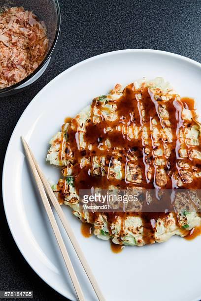 plate with okonomiyake and chopsticks - okonomiyaki stock pictures, royalty-free photos & images