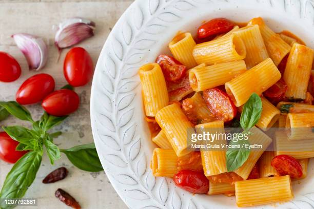 a plate with pasta with cherry tomatoes and basil from above. - maria giulia vincenti foto e immagini stock