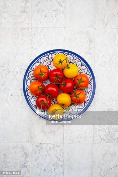 plate with red, orange, and yellow tomatoes - larissa veronesi stock-fotos und bilder