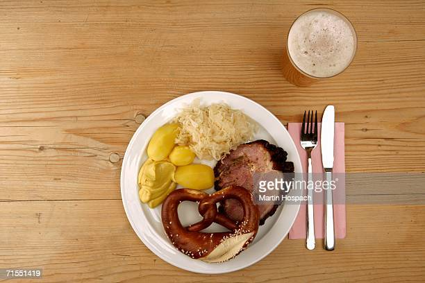 Plate with roast pork, sauerkraut, potato, and pretzel next to glass of beer