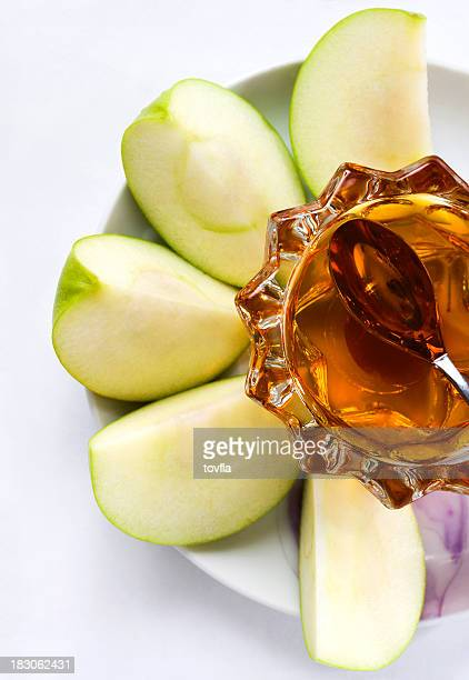 A plate with sliced apples and honey on it