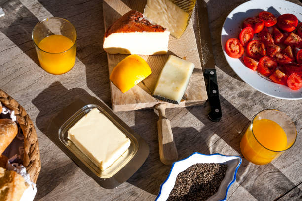 Plate with sliced tomatoes, two glasses of orange juice, butter, pepper and cutting board with different cheese