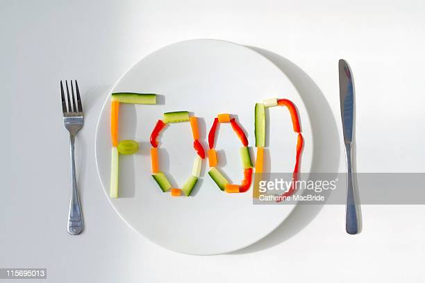 plate with word food written in vegetables - catherine macbride stock pictures, royalty-free photos & images