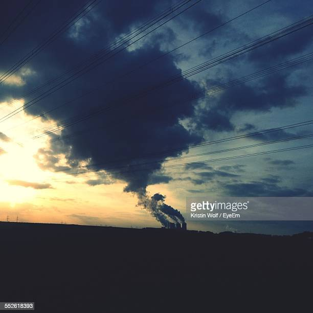 Plateau With Industrial Chimneys On Horizon At Dusk, Smoke, Clouds And Electric Lines In Sky