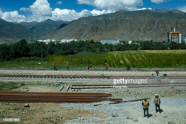 Platelayers work to maintain rail taken in a train carriage of from Beijing to Lhasa on August 15 2012 in Lhasa China After QinghaiTibet Railway went...
