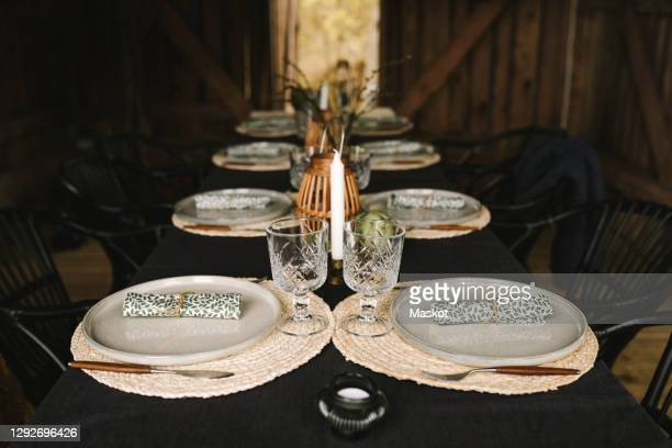 plates and glasses arranged on dining table for dinner party - candlelight stock pictures, royalty-free photos & images