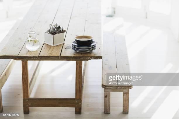 Placas e Cutelaria empilhados sobre a mesa de madeira Aliança