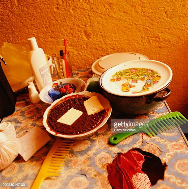 Plates and toiletries on table with bowl of beans with bread