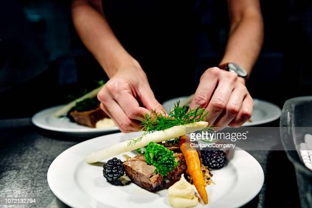 plates at the pass ready to be served. - fine dining stock pictures, royalty-free photos & images