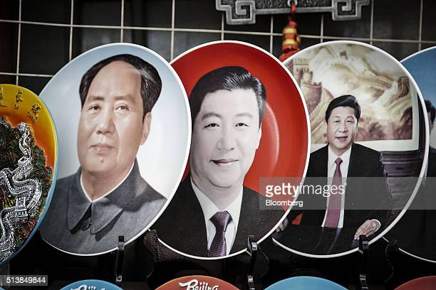 Plates featuring a portrait of former Chinese leader Mao Zedong left and portraits of Xi Jinping China's president sit on display at a street market...