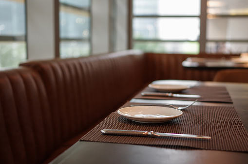 Plates, forks and knifes on restaurant table mat with leather sofa near window in daylight 1158554774