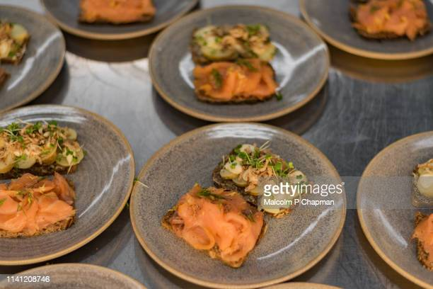 Plates of Danish Smorrebrod (Smørrebrød) - open sandwiches with smoked salmon and potato