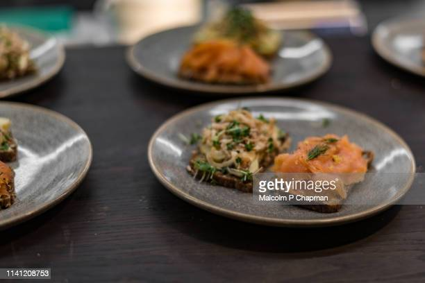 plates of danish smorrebrod (smørrebrød) - open sandwiches with smoked salmon and potato - danish culture stock pictures, royalty-free photos & images