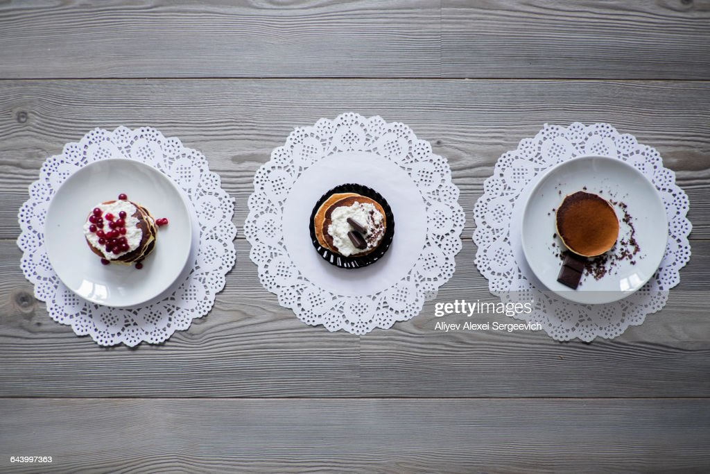 Plates of dessert on lace doilies : Stock Photo