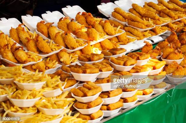 plates of fried food for sale in market - unhealthy eating stock pictures, royalty-free photos & images
