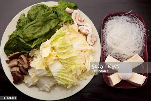 Plates of mushrooms, lettuce, egg, tofu and noodles