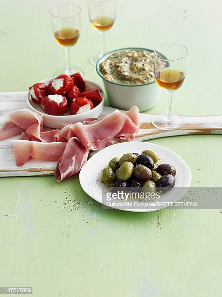 Plates of olives, peppers and dip