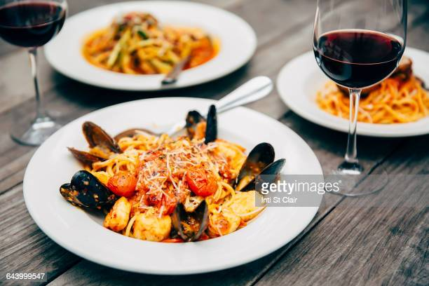 plates of seafood and pasta with wine glasses - seafood stock pictures, royalty-free photos & images