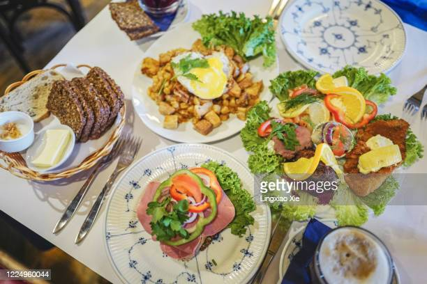 plates of traditional danish smørrebrød or open sandwiches with biksemad and breads, landmark of copenhagen, denmark - tradition stock pictures, royalty-free photos & images