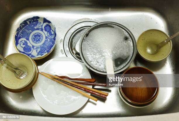 Plates stacked and cutlery in kitchen sink