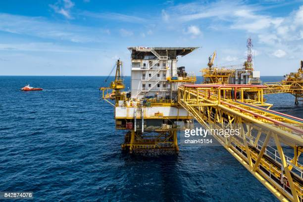 platform offshore oil and gas processing platform for oil and gas industry to treat gases and sent to onshore refinery, petrochemical and power generation plant with transportation boat. industry concept. - planta petroquímica fotografías e imágenes de stock