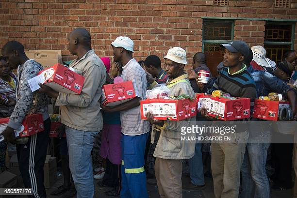 Platinum sector striking miners queue to receive food parcels delivered at the St Mark church from the South African food Bank on June 13 2014 in...