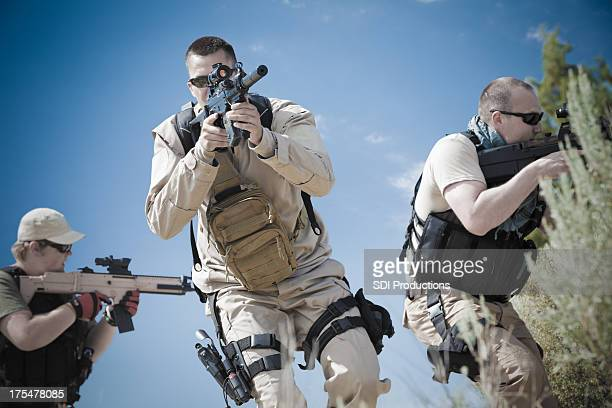 Platoon of military soldiers using weapons during training exercise
