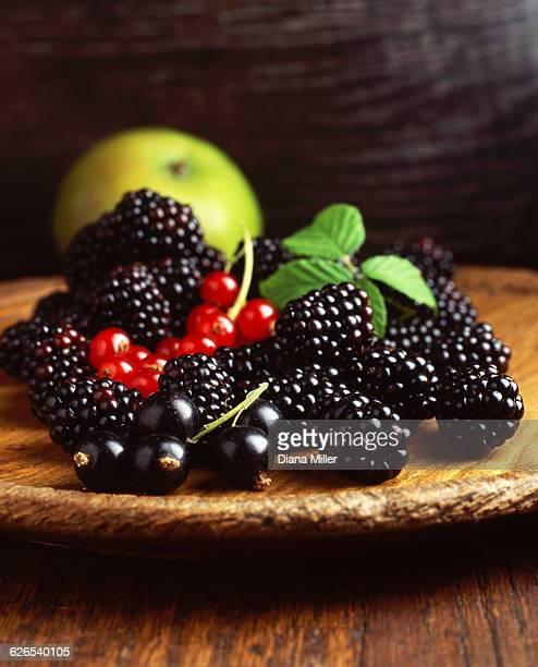 Platter of blackberries, red currants, blackcurrants, apple on table