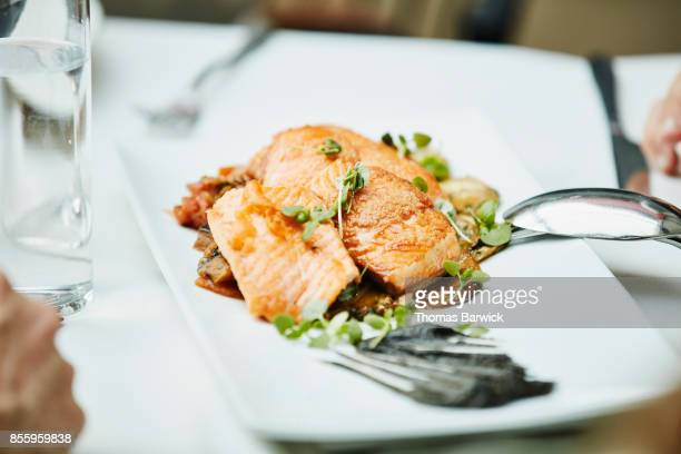 Platter of seared wild salmon on restaurant table during family style meal