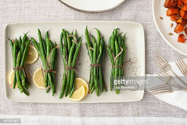 platter of strung bunches of green beans w/lemon - green bean stock pictures, royalty-free photos & images